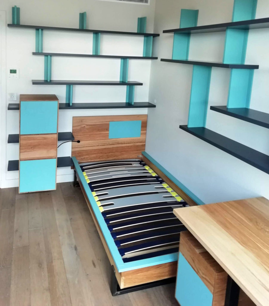 Mobilier de chambre sur mesure : bureau, lit, rangement de chevet et étagères murales.